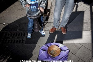 Napoli, 17/02/2012. A children begging  money playing a drum with his father.