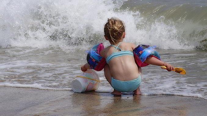Bambino gioca sulla riva in spiaggia