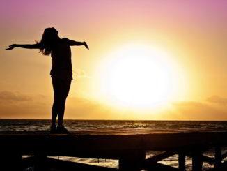 Donna al mare di fronte al tramonto